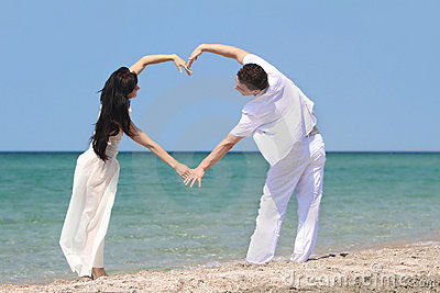 Couple making heart by arms on beach