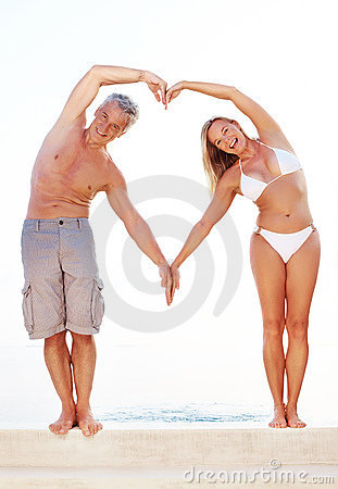 Couple making heart shape with arms by the pool