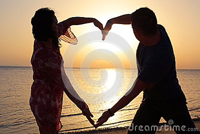Couple making romantic heart shape at sunrise
