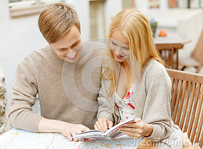 Couple with map, camera and city guide in cafe