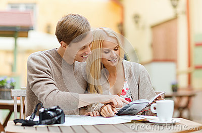 Couple with map, camera, city guide and coffee