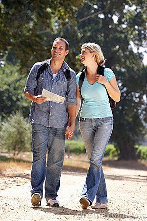 Couple with map walking in country