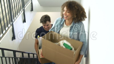 Couple Moving Into New Home Carrying Box Upstairs Stock