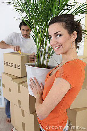Couple moving plant into home