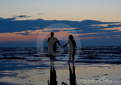 Couple near sea at sunset.