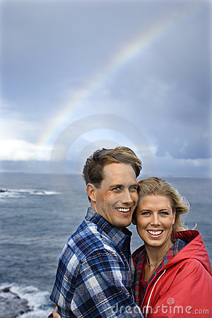 Couple by ocean and rainbow in Maui, Hawaii.