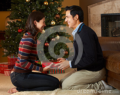 Couple Opening Presents In Front Of Christmas Tree