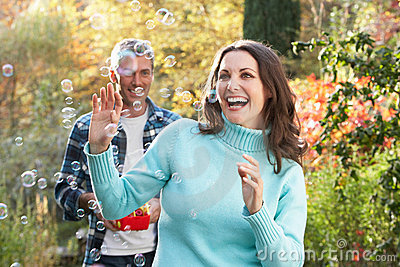 Couple Outdoors With Bubble Machine