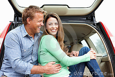 Couple outdoors with car