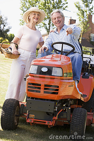 Couple outdoors with tools and lawnmower pointing