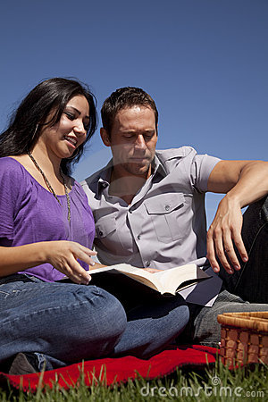 Couple outside reading book