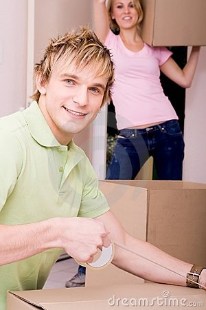Couple packing boxes to move