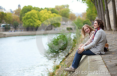 Couple in Paris, sitting at the edge of water