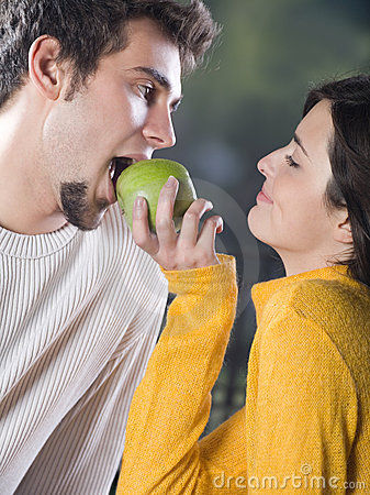 Couple playfully eating apple