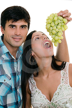 Couple playfully eating grapes