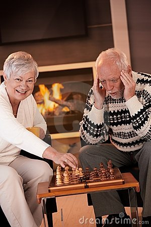 Couple playing chess in cosy living room