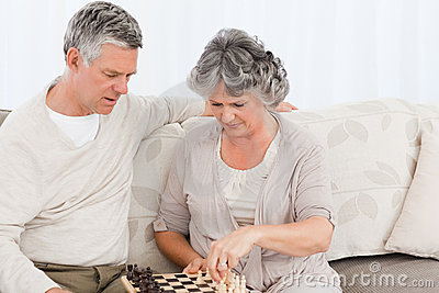 Couple playing chess on their sofa