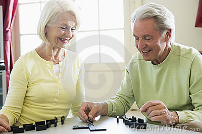 Couple playing dominos in living room smiling