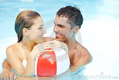 Couple in pool with beach ball