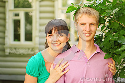Couple pose near wooden village house
