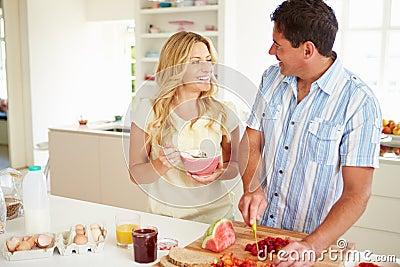 Couple Preparing Healthy Breakfast In Kitchen