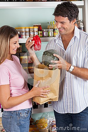 Couple Putting Bellpepper And Pumpkin In Paper Bag