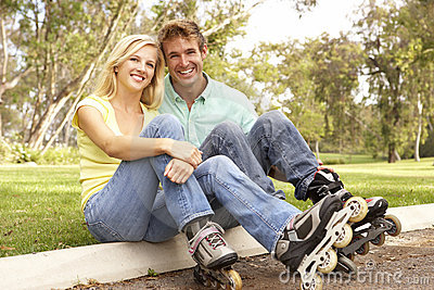Couple Putting On In Line Skates In Park