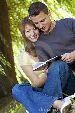 Couple reading a book in park