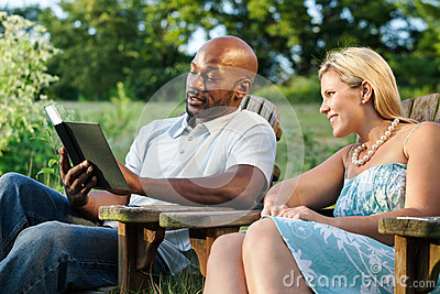 Couple reading a book at the park