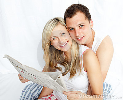 Couple reading a newspaper in bed