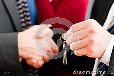 Couple receiving keys from real estate broker