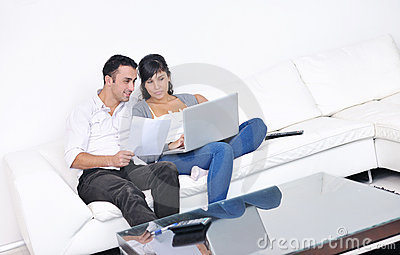 Couple relax and work on laptop computer at home