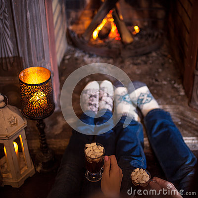 Free Couple Relaxing At Home Drinking Cocoa. Feet In Wool Socks Near Fireplace. Winter Holiday Concept Royalty Free Stock Photography - 81505157