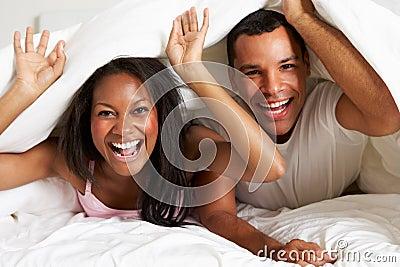 Couple Relaxing In Bed Hiding Under Duvet