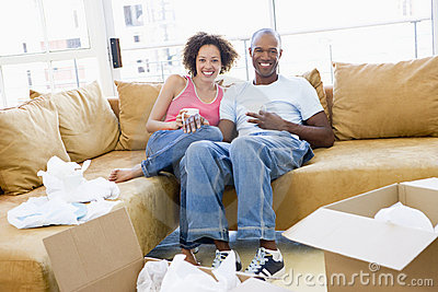 Couple relaxing with coffee by boxes in new home