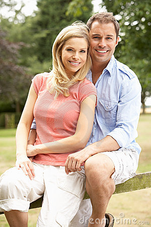 Couple Relaxing In Countryside Sitting On Fence