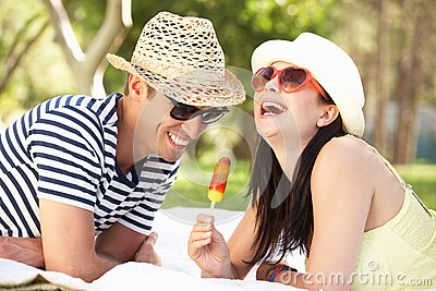 Couple Relaxing In Garden Eating Ice Lolly