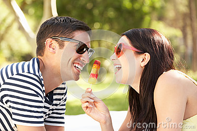 Couple Relaxing In Garden Eating Lolly