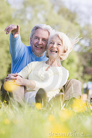 Couple relaxing outdoors pointing and smiling