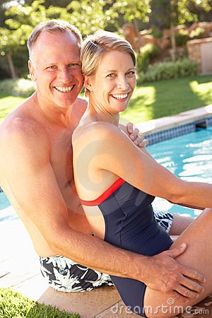 Couple Relaxing By Pool In Garden