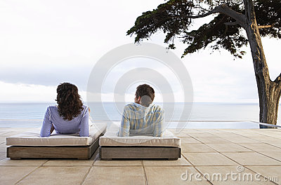Couple Relaxing On Sunbeds By Infinity Pool
