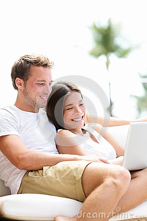 Couple relaxing together in sofa with laptop pc