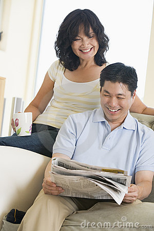 Free Couple Relaxing With A Newspaper And Smiling Stock Image - 5534721