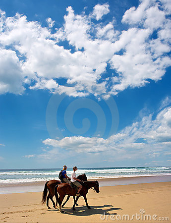 Couple of riders on beach under dramatic skies
