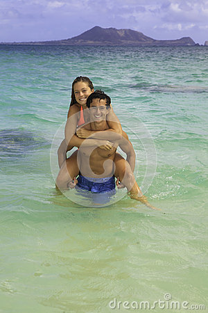 Couple riding piggyback in the ocean