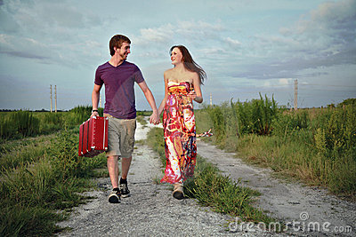 Couple on road with suitcase