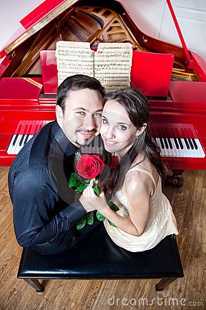Couple with rose near red piano