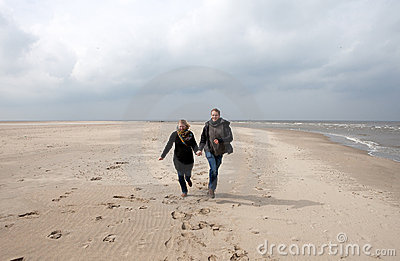 Couple is running on the beach