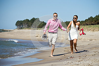Couple running on beach by sea