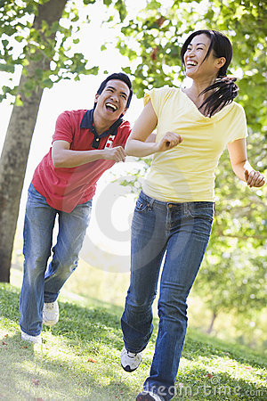 Couple running and being playful outdoors smiling